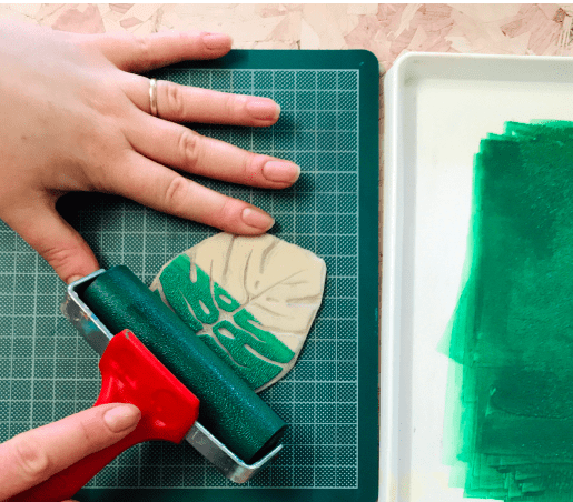 roller being used to apply green block printing ink to carved monstera leaf