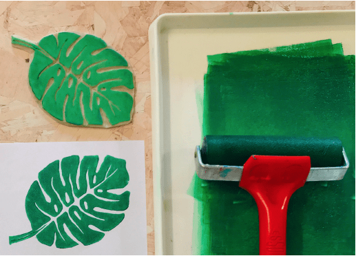 ink tray with green ink, roller, and piece of lino cut into a monserta leaf