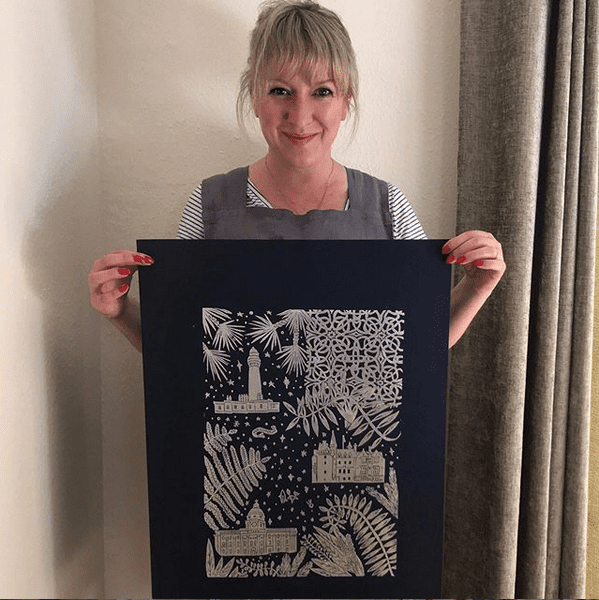 A lady called Hayley, from Buff and Blue Prints, holding a lino black and gold lino print