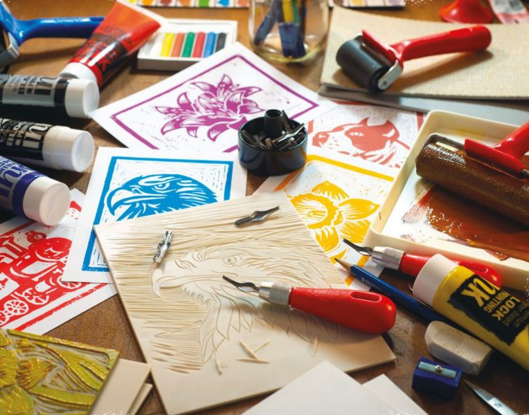 selection of inks, softcut, and carving materials laid out on a table