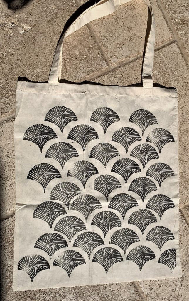 White tote bag printed with repeated geometric design in black