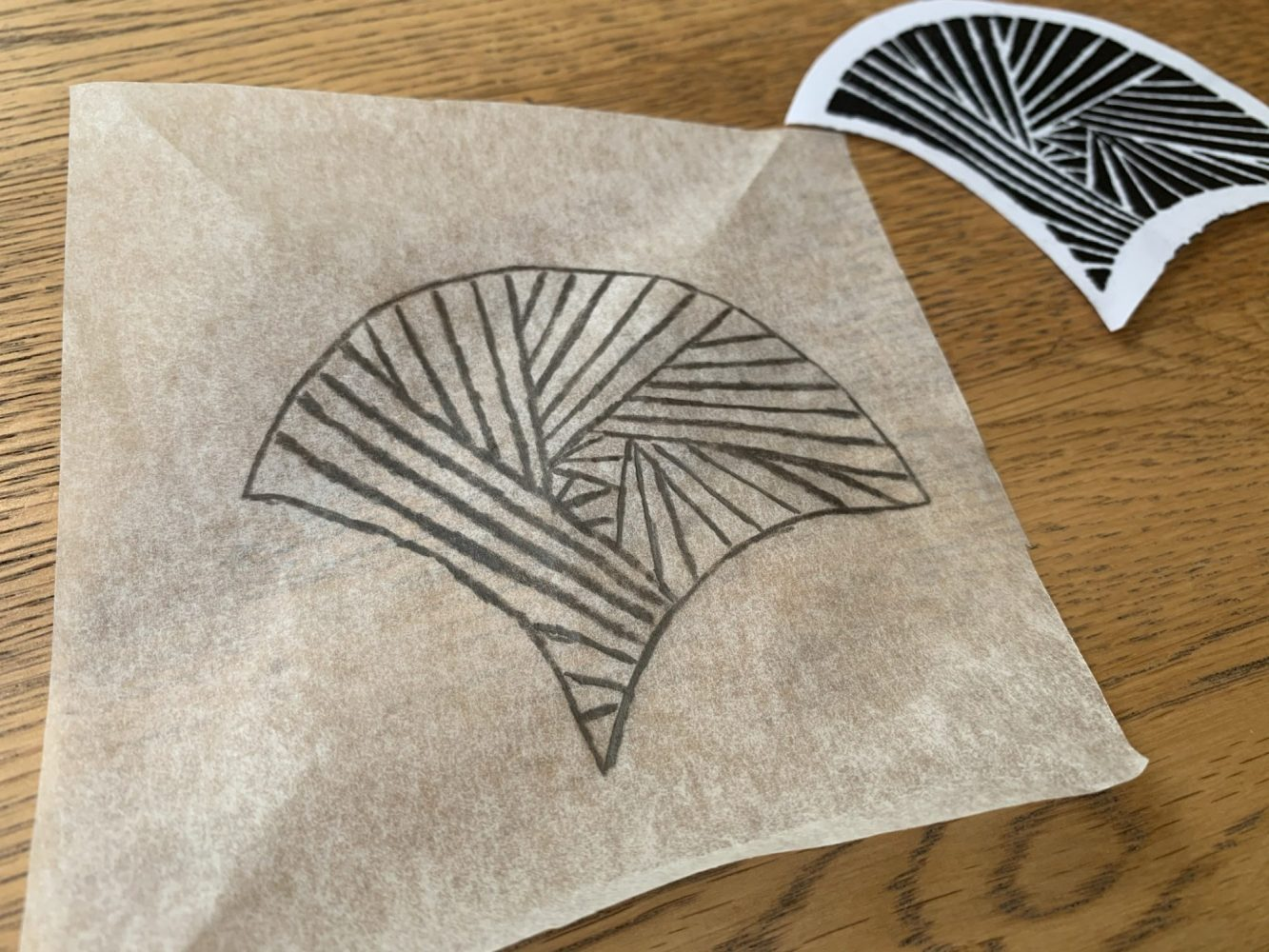 Geomertic fan shap drawn in pencil on a piece of tracing paper