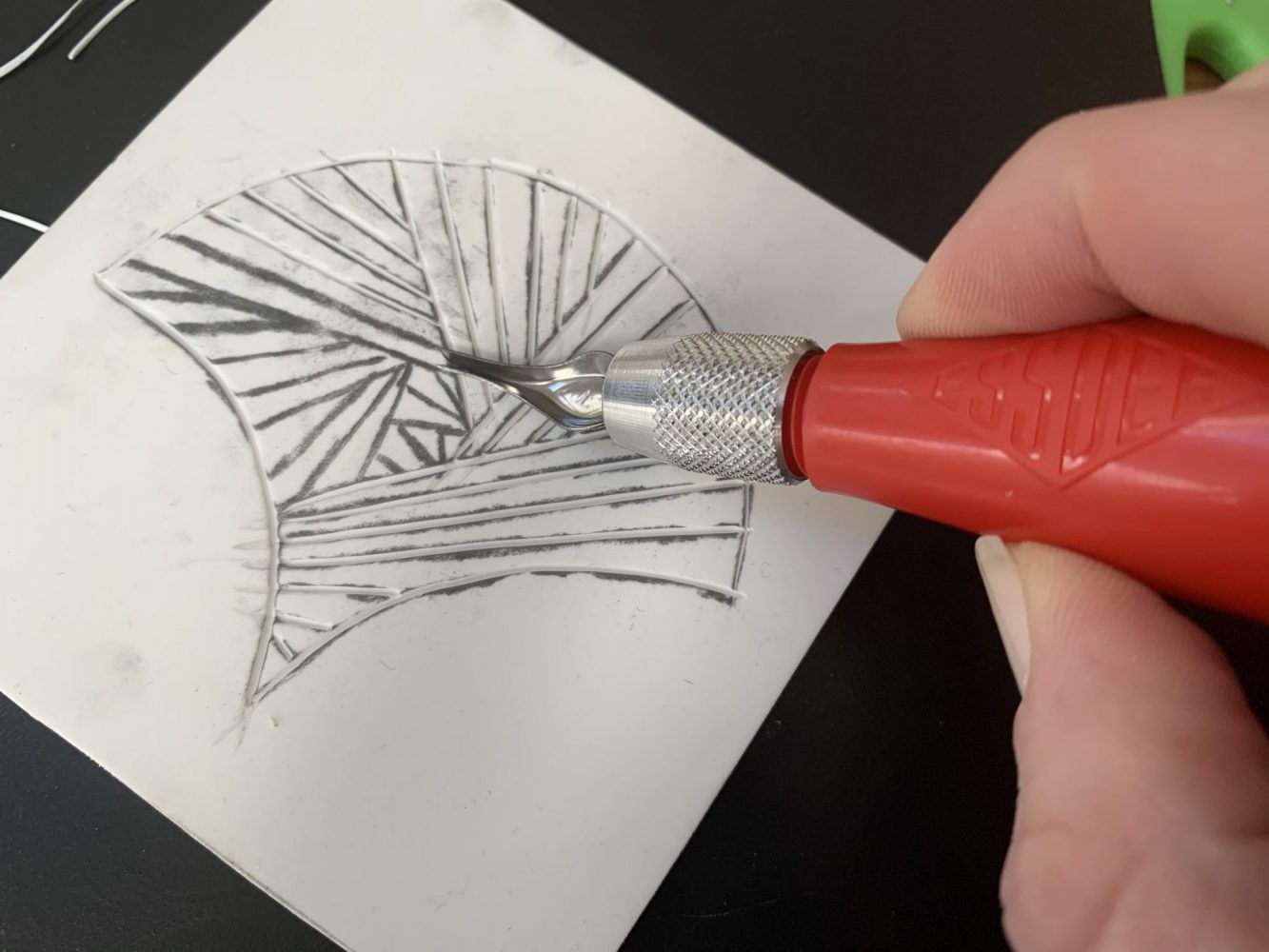 Lino cutter being used to carve edge of fan design