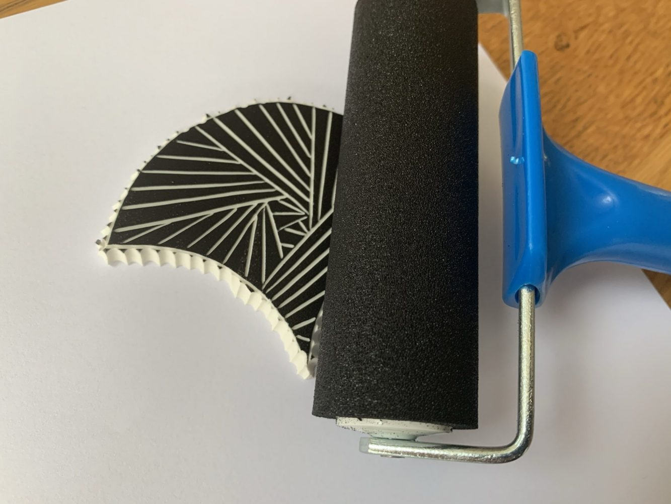 Black fabric ink being transferred onto fan design using a fabric roller