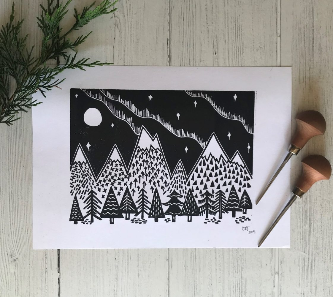 Linoprint of mountains and trees in black and white