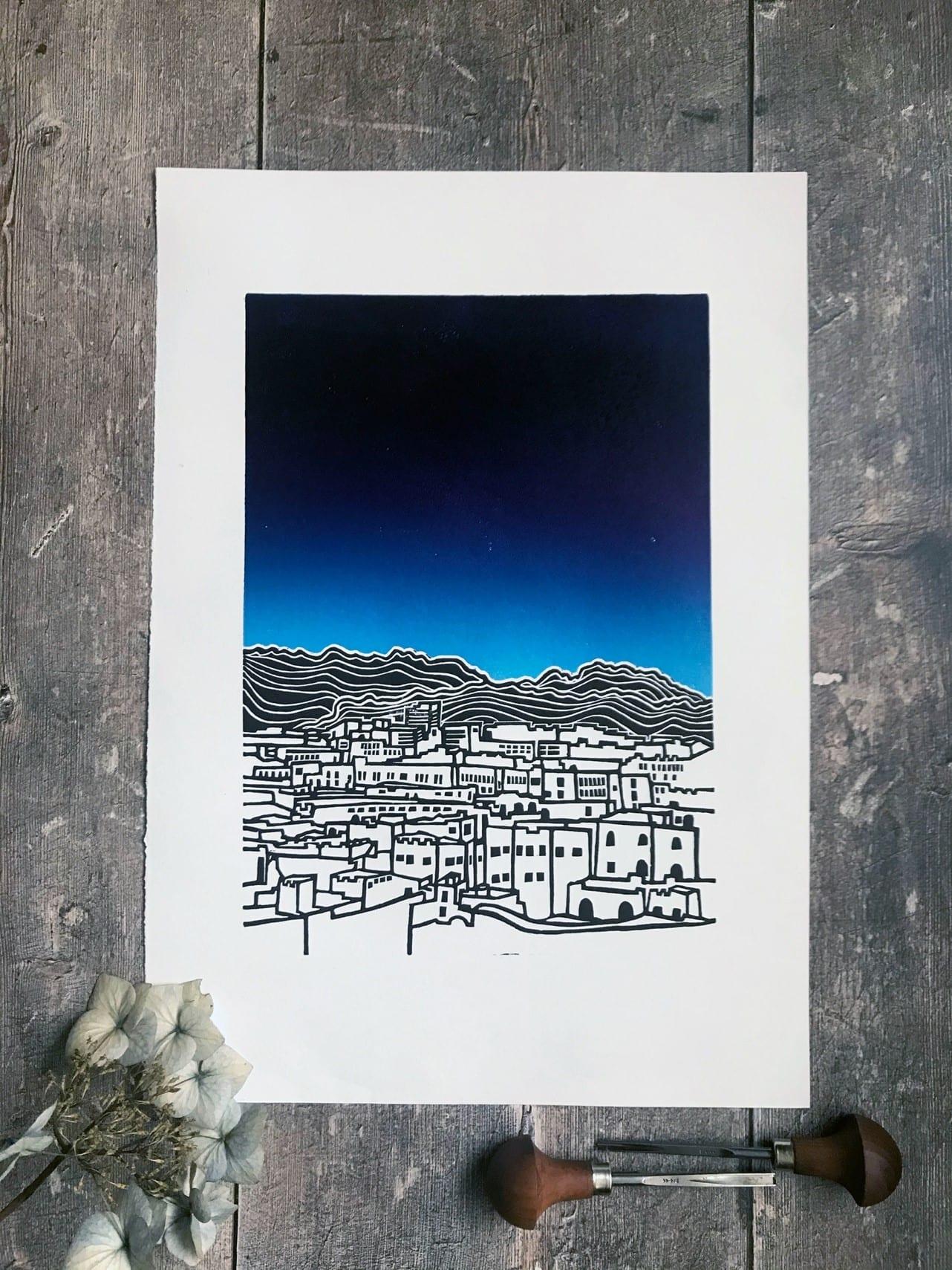 Lino print of city with a brilliant blue sky